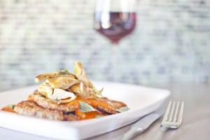 Pan-fried pork chop with artichoke confit, tomato and oregano paired with a tall glass of fine wine.