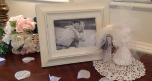Paper doilies, fake (recyclable) rose petals, and framed pictures of the couple make easy decorations.